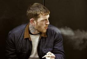 young caucasian man with tattoo on neck smoking