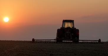 tractor in the field at dusk