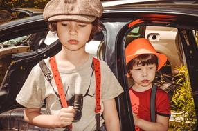 retro photo of two boys on the background of an old car