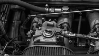 black and white photo of a carburetor in a car