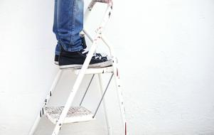 male legs on Ladder at wall
