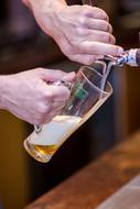 a man pouring beer into a glass