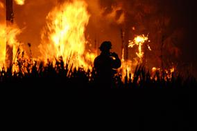 silhouette of a firefighter on a background of fire on the field