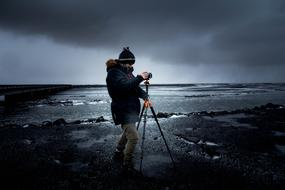 Photographer with Camera on Tripod at sea on stormy weather