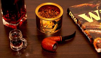 tobacco, smoking pipe and brandy on the table
