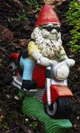 Colorful garden dwarf on the motorcycle among the plants