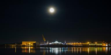 night photo of an industrial shipyard under the moon