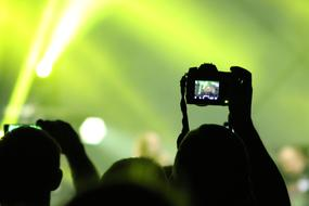 crowd is filming a concert on video