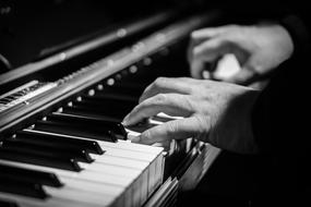 black and white photo of a man playing the piano