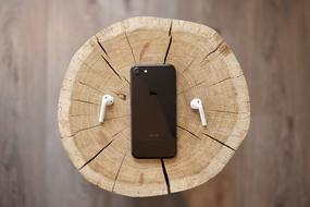 smartphone and headphones lie on a stump