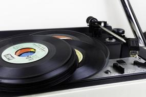 a stack of vinyl records lies on a gramophone