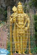 standing warrior, fenced ancient golden buddhist Sculpture, malaysia