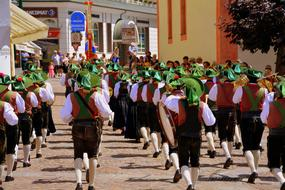 Music Band in traditional clothing marching on street in city, italy, south tyrol