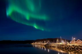 green Northern Lights in deep blue sky above illuminated village