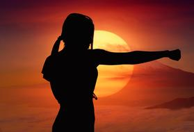 karate girl silhouette on sunset background