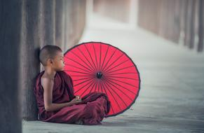 young Buddhist Monk sits on ground near red umbrella