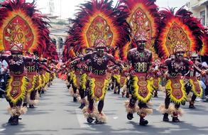tribal men in carnival costumes parading on Street, Philippines, iloilo