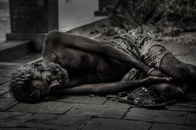 black and white photo of a naked homeless man on the street