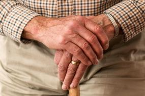 hands of an elderly man with a wedding ring