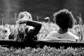 black and white photo of two girlfriends on a bench