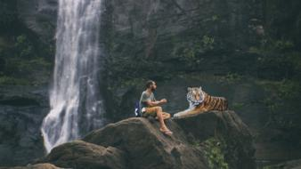 photo of a man and a tiger on the rocks against the background of a waterfall