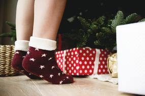 Christmas Celebration, female legs at gift boxes and fir tree