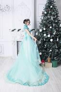 young girl in long green dress posing at Christmas Tree