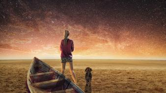 fantastic image of a girl, a wooden boat and a puppy on the beach against the starry sky