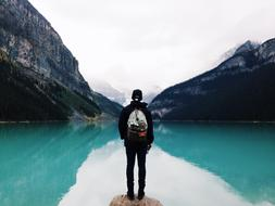 man with backpack near mountain lake with turquoise water