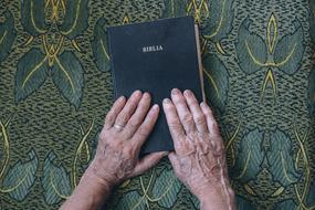 two hands of an elderly man on the bible