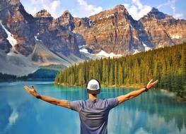 Man with wide open hands at scenic mountain lake, canada