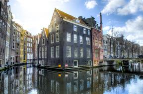 old buildings mirroring on water at winter, netherlands, amsterdam