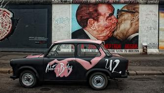 vintage car at graffiti on Berlin Wall East Side gallery, germany