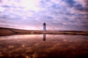 Lighthouse on coastline at scenic evening sky