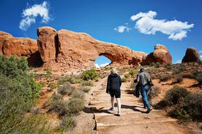 woman and man walking on path to scenic Red Rocks, usa, Utah, Moab