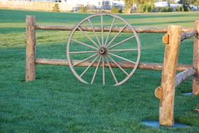 antique wheel stands at a wooden fence
