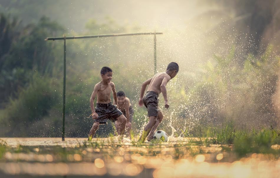 Children are playing football at rainy day