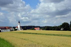 Village with church behind crops field, germany, bavaria