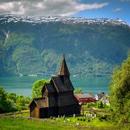 aged Stave Church on side of scenic Fjord at Mountain, norway, urnes