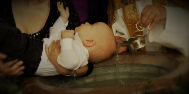 baby on hands of mother above Baptismal Font in Church
