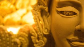 Buddha statue head on the background of burning candles
