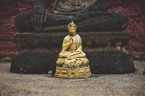 golden buddha statue on the background of a stone statue