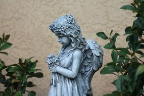 Beautiful girl angel statue with flowers among the green leaves