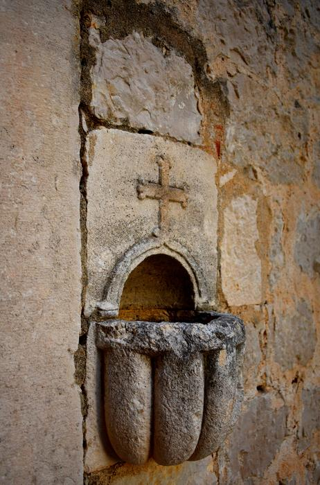 cross, stone carving on wall above holy water fountain