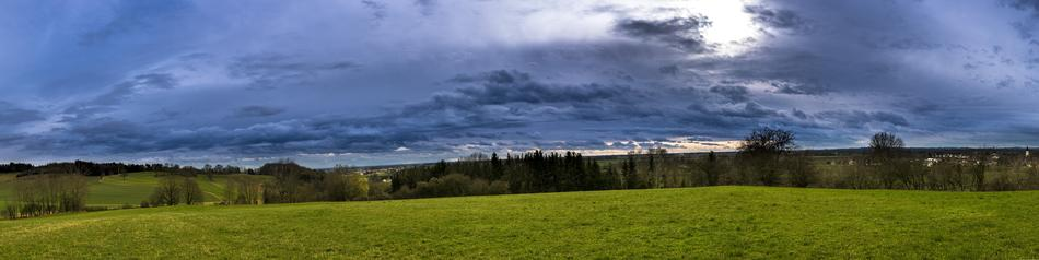 Panoramic rural view, farmland beneath stormy clouds