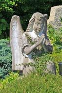 sculpture of an angel in a green plant