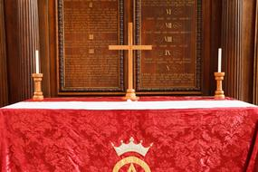 candles and a cross on the red altar