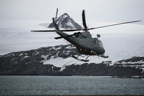 Helicopter above sea at snowy coast