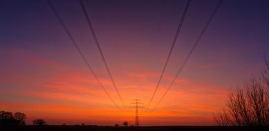 reinforced power lines against a background of orange-blue evening sky