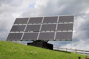 solar panels on the side of a green hill